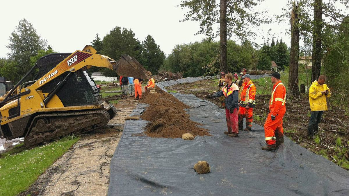 In this photo released by the RCMP, workers build a temporary dike to contain water near Slake Lake, Alta. on Saturday July 11, 2011.