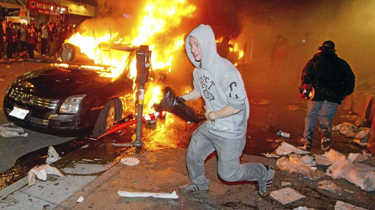 A behoodied looter from the Bay runs past a burning car during the Stanley Cup riot in Vancouver on June 15, 2011.