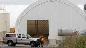 An RCMP officer and an unknown official talk in front of tent containing manure at a mushroom farm in Langley, B.C., on Sept. 6, 2008, after three people were overcome by an unknown substance and died and three were seriously injured.