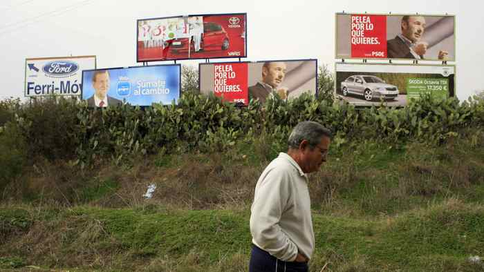 A man walks past electoral posters of Prime ministerial candidate Alfredo Perez Rubalcaba of the Spanish Socialist Workers' Party (Partido Socialista Obrero Espanol) and Spain's centre-right People's Party (Partido Popular) leader Mariano Rajoy in Camas, next to Seville November 16, 2011.
