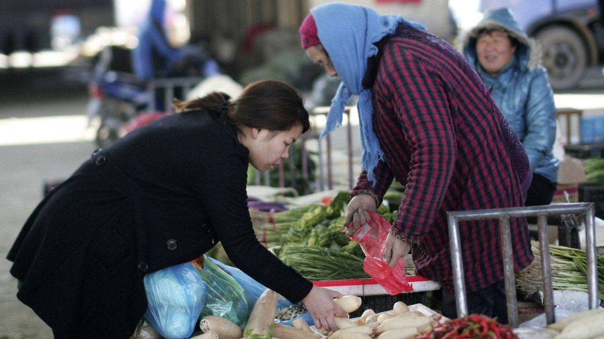 A woman buys vegetables at a market Friday Dec. 9, 2011 in Shanghai, China. China's chronically high inflation rate fell to a lower than expected 4.2 percent in November, allowing wider leeway for Beijing to ease credit to support growth.
