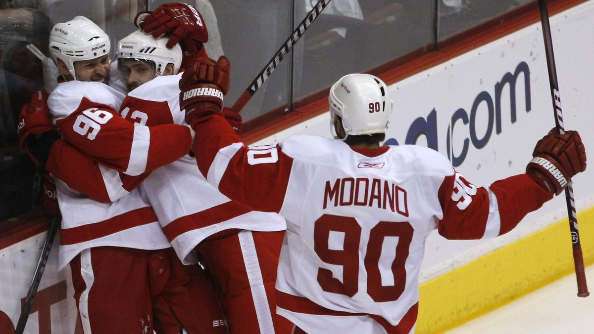 Detroit Red Wings left wing Tomas Holmstrom, left, celebrates with teammates Pavel Datsyuk and Mike Modano after scoring a first period goal during Game 4.
