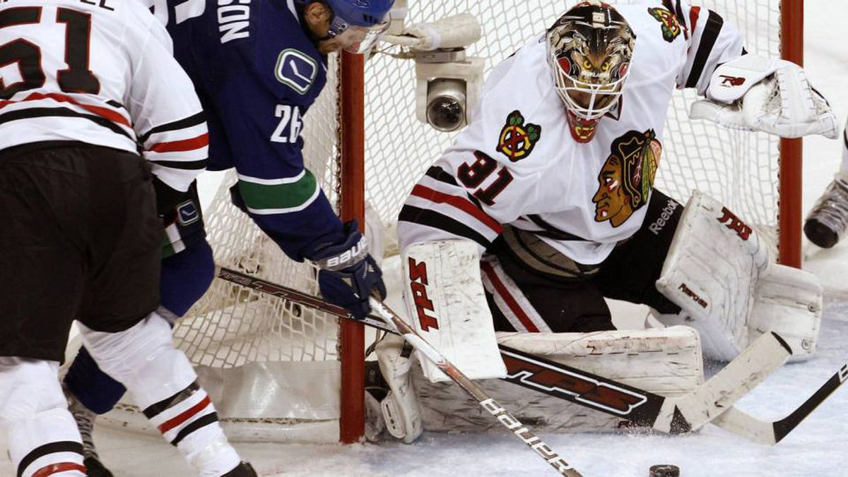 Chicago Blackhawks goalie Antti Niemi makes a third period save on Vancouver Canucks right wing Mikael Samuelsson as Blackhawks' Brian Campbell (51) checks during Game 3 of their NHL Western Conference semi-final hockey game in Vancouver, British Columbia May 5, 2010.