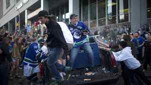 Canucks fans riot at the corner of Hamilton Street and Georgia Street after the Bruins won the Stanley Cup in Vancouver
