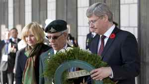 Prime Minister Stephen Harper places a wreath with Canadian Veteran Arsene Dube and Laureen Harper during a Rememberance Day ceremony at the Korean War Memorial in Seoul, Korea Thursday Nov.11, 2010.