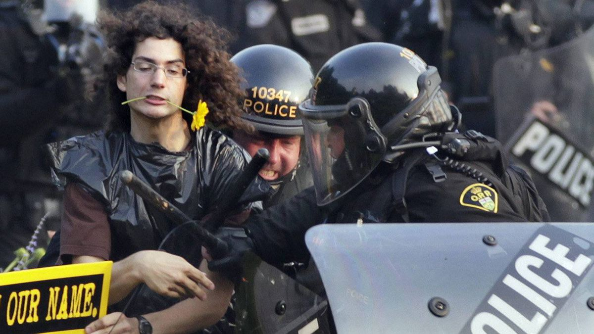 In this June 27, 2010 file photo, a protester with a daisy clenched in his teeth is seized by riot police during protests at the G8 and G20 Summits in Toronto.