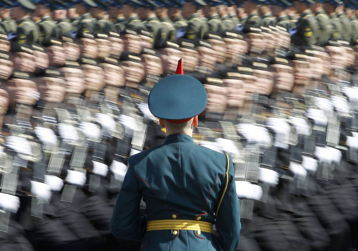 A Russian soldier stands at attention as troops march past during a general rehearsal for the upcoming Victory Day parade at Moscow's Red Square May 6, 2012.