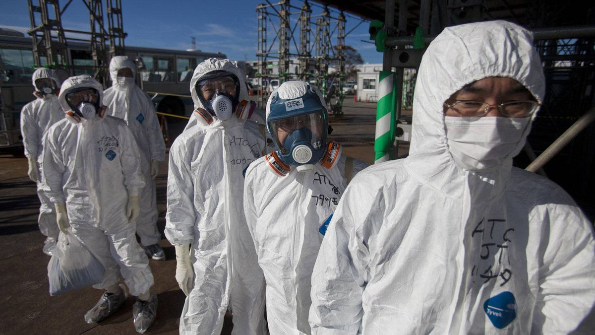 Workers in protective suits and masks wait to enter the emergency operation center at the crippled Tokyo Electric Power Co. (Tepco) Fukushima Dai-Ichi nuclear power station in Okuma Town, Fukushima Prefecture, Japan, on Saturday, Nov. 12, 2011. Tepco is struggling to contain the worst nuclear disaster in 25 years.
