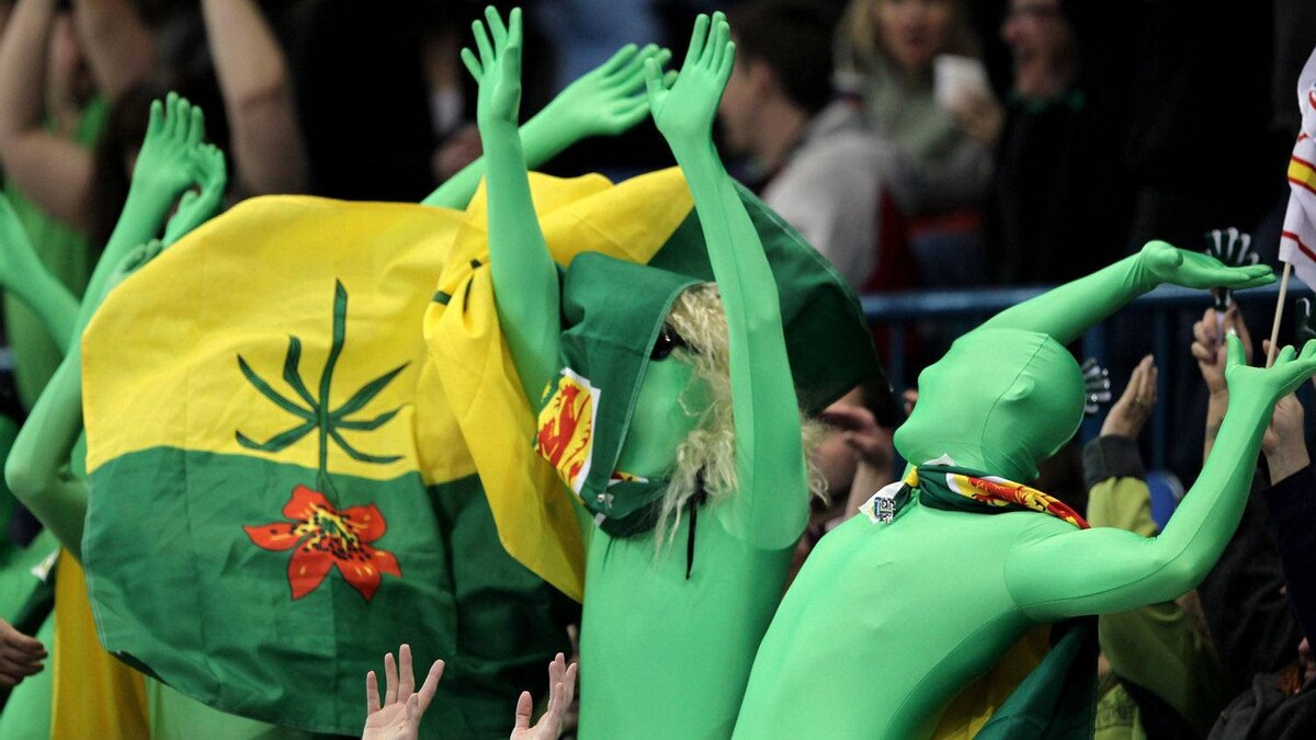 Saskatchewan fans wearing green body suits do the wave during the evening draw at the Tim Hortons Brier in Saskatoon on Saturday, March, 3, 2012. THE CANADIAN PRESS/Jonathan Hayward