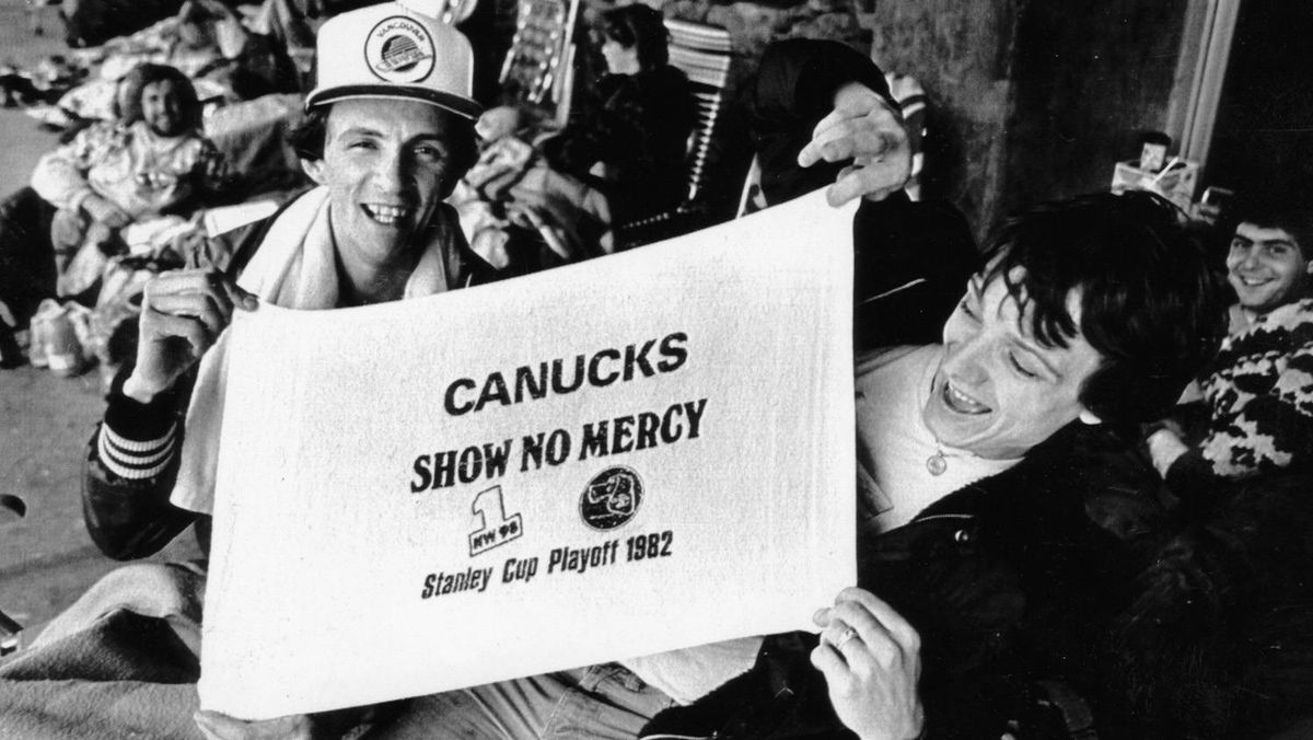 A couple of Canuck fans proudly display one of the towels that they and thousands of others will use to cheer on the Canucks in their first home game of the Stanley Cup playoffs in Vancouver on May 13, 1982.