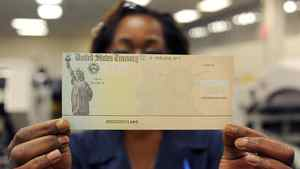 A U.S. Treasury Department employee holds a blank U.S. Treasury cheque before it's run through a printer in Philadelphia.