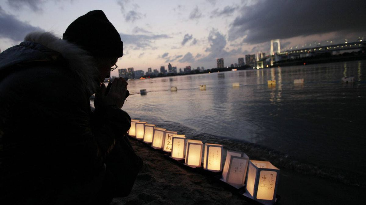 A man prays beside lanterns placed at the waterfront in Tokyo Bay to mark the first anniversary of the earthquake and tsunami which devastated northeast Japan.