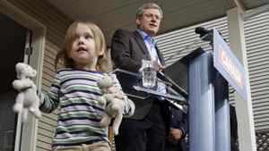 Prime Minister Stephen Harper speaks as 2.5-year-old Fiona Wellburn plays with her toys during a campaign stop in Saanich, B.C., on March 28, 2011.