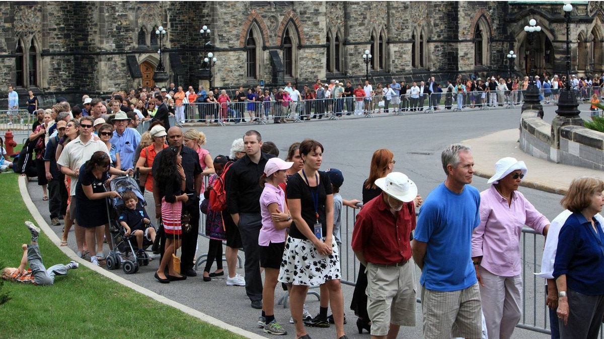 Members of the public line up on Parliament Hill to pay their respects to Mr. Layton.