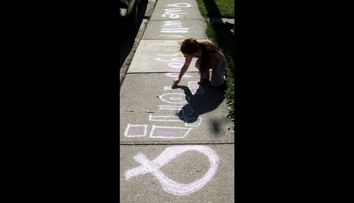 "Sarah Ditchfield writes ""We will miss you Tori"" on the sidewalk near Victoria ""Tori"" Stafford's home on May 20, 2009."