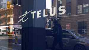 A pedestrian is reflected in the window of a Telus store while using a mobile phone in Ottawa February 11, 2011.