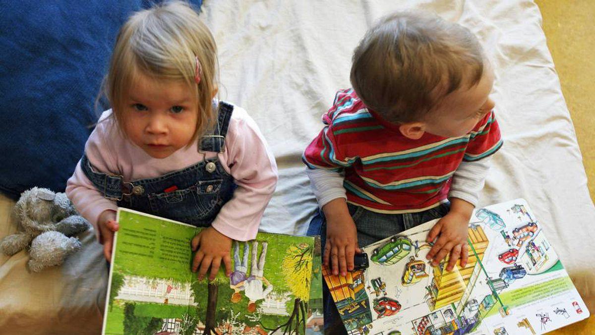 Children look at picture books at a kindergarten in Berlin.