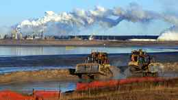 Workers use heavy machinery in the tailings pond at the Syncrude oil sands extraction facility near Fort McMurray.