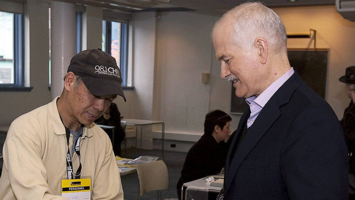 NDP Leader Jack Layton receives his ballot from a worker at a voting station in Toronto on Monday, May 2, 2011.