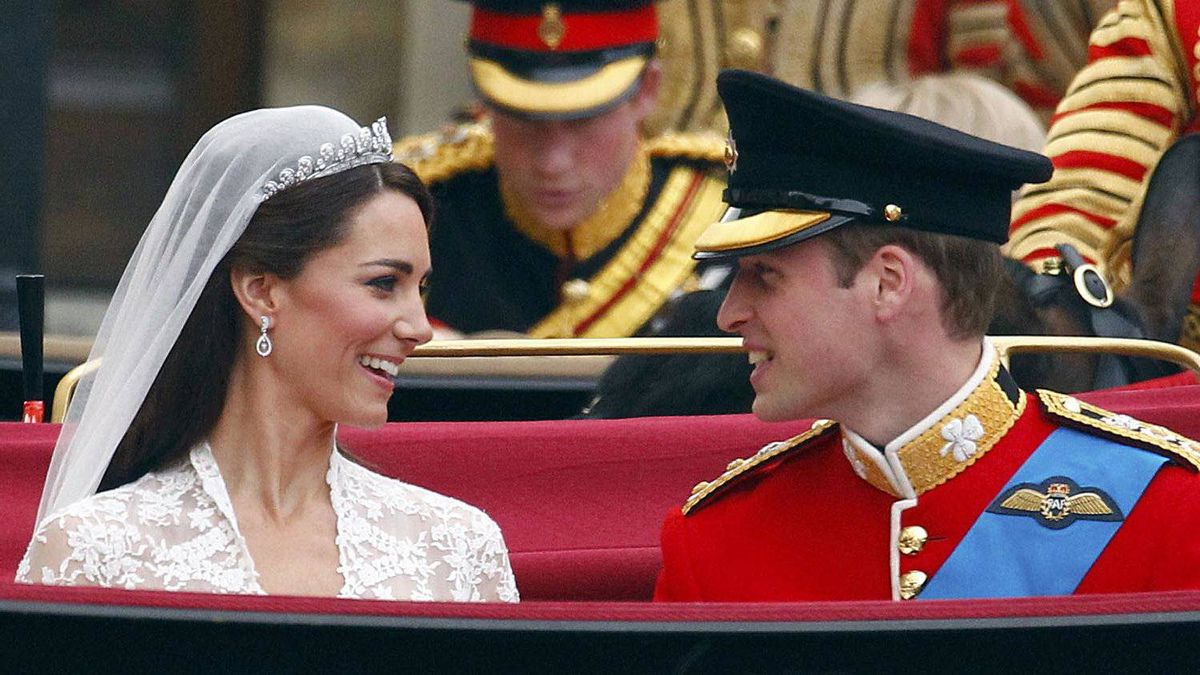 Britain's Prince William, and Catherine, Duchess of Cambridge smile as they travel to Buckingham Palace in the 1902 State Landau, along the Procession Route, after their wedding in Westminster Abbey, in central London April 29, 2011.