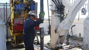 A worker at EnCana's Frenchie Draw gas-drilling rig in central Wyoming guides sections of steel pipe into a well.