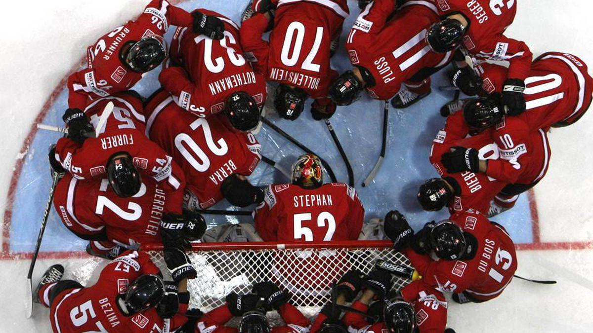 Switzerland's team gather near the goal before their 2012 IIHF men's ice hockey World Championship game with Belarus.
