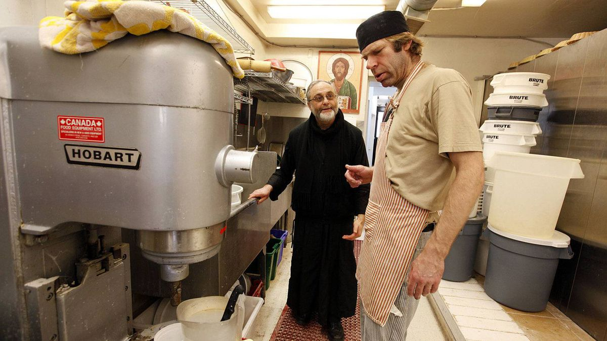 Father Roberto Ubertino, executive director of St. John the Compassionate Mission, talks with baker John Kipphoff at St. John's Bakery on Broadview Ave. in Toronto. Bakery staff use organic ingredients and 200-year-old recipes from Brittany to produce their handmade bread.