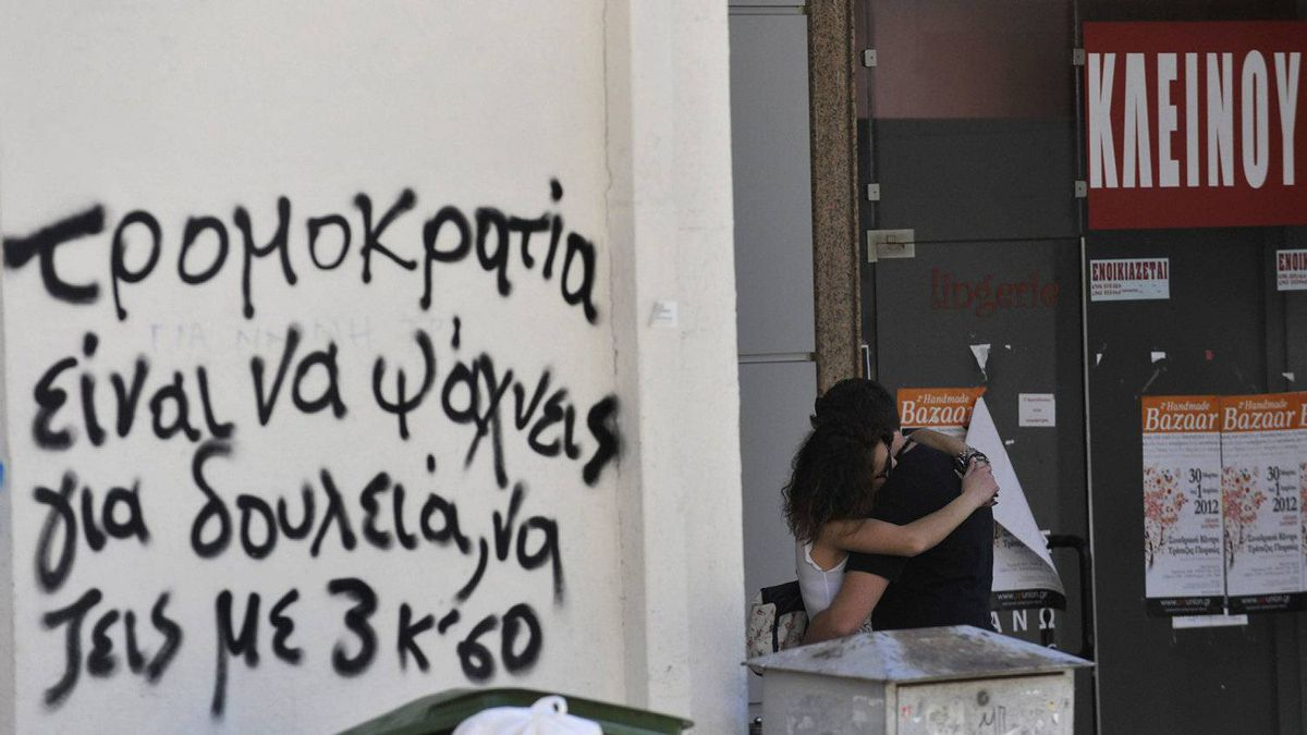 A couple hug in front of a shuttered shop in Thessaloniki, Greece. The partially obscured slogan, in Greek, reads 'Terrorism is to be looking for work, and to live with peanuts.'