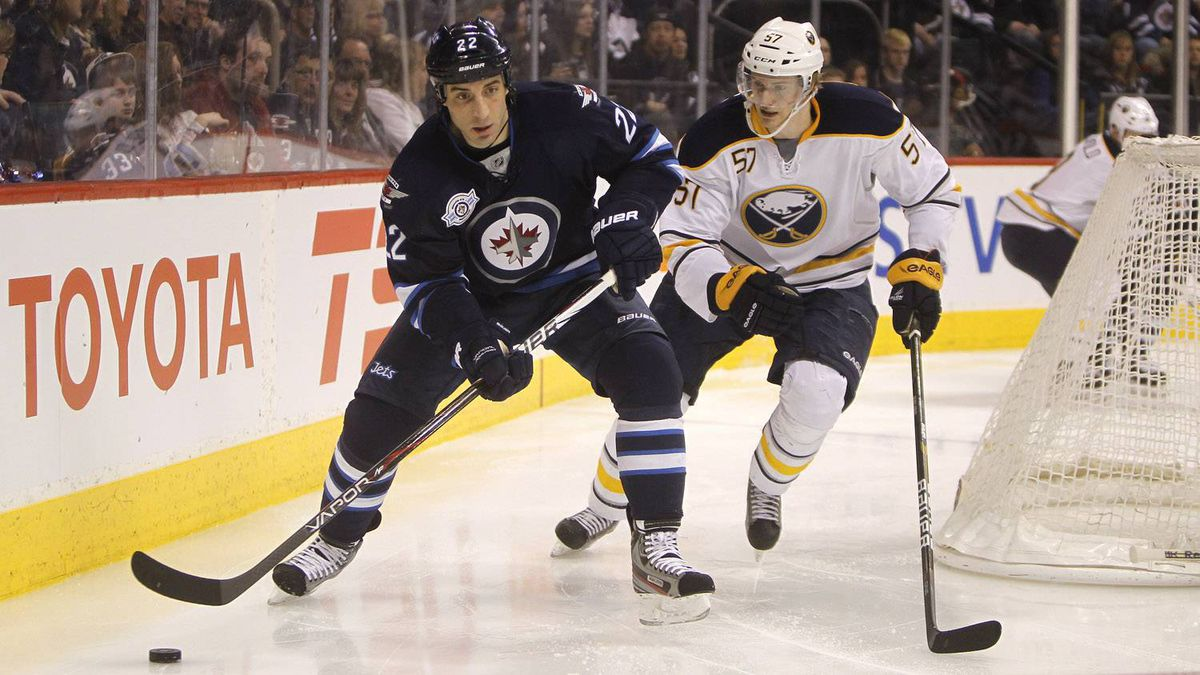 Winnipeg Jets' Chris Thorburn and Buffalo Sabres' Tyler Myers battle for the puck behind the Buffalo net during the second period.