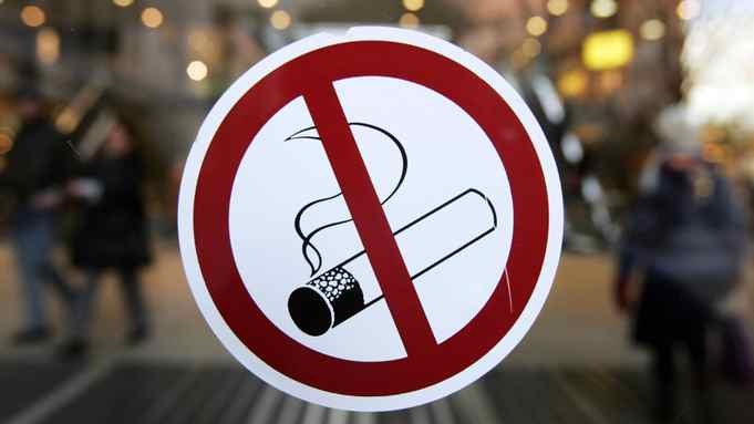 A sticker with a no smoking sign adorns the glass door of a Berlin shopping mall 31 January 2008.