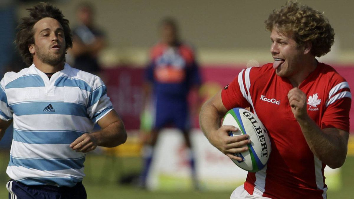 Canada's Conor Trainor, center, sticks out his tongue as Argentina's players run behind as he goes on to score during a men's gold medal rugby match at the Pan American Games in Guadalajara, Mexico, Sunday, Oct. 30, 2011. Canada won the gold and Argentina took the silver. (AP Photo/Jorge Saenz)