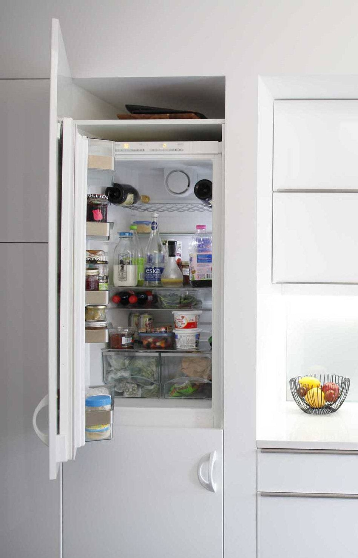 The refrigerator is hidden behind high-gloss IKEA cabinetry to keep visual clutter to a minimum.