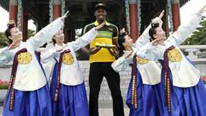 World record holder Usain Bolt (C) of Jamaica poses with his new running spikes and promoters wearing traditional Hanbok in Daegu, southeast of Seoul August 20, 2011. Bolt, the world's fastest man, will compete in the World Athletics Championships in Daegu, held from August 27-September 4. He predicted on Saturday he would retain his world 100 metres title in Daegu easily, provided he gets a decent start. Picture taken August 20, 2011. REUTERS/Lee Jae-Won