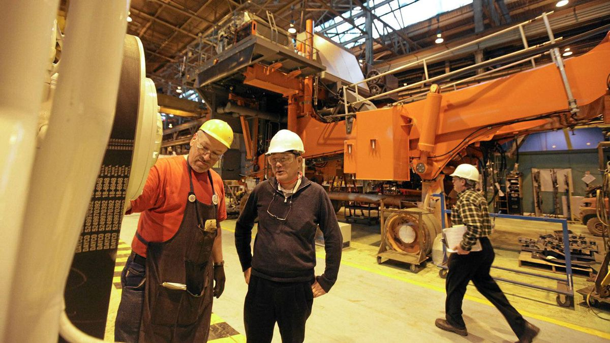 Hideo Kitawaki, centre, CEO of Hitachi Construction Truck Manufacturing Ltd. in Guelph Ont., talks with engine assembler Ralph Schmidt, left, near one of their 3,000-horsepower motors used in dump trucks such as the EH 5000 trucks with load capacity of more than 300 tons.