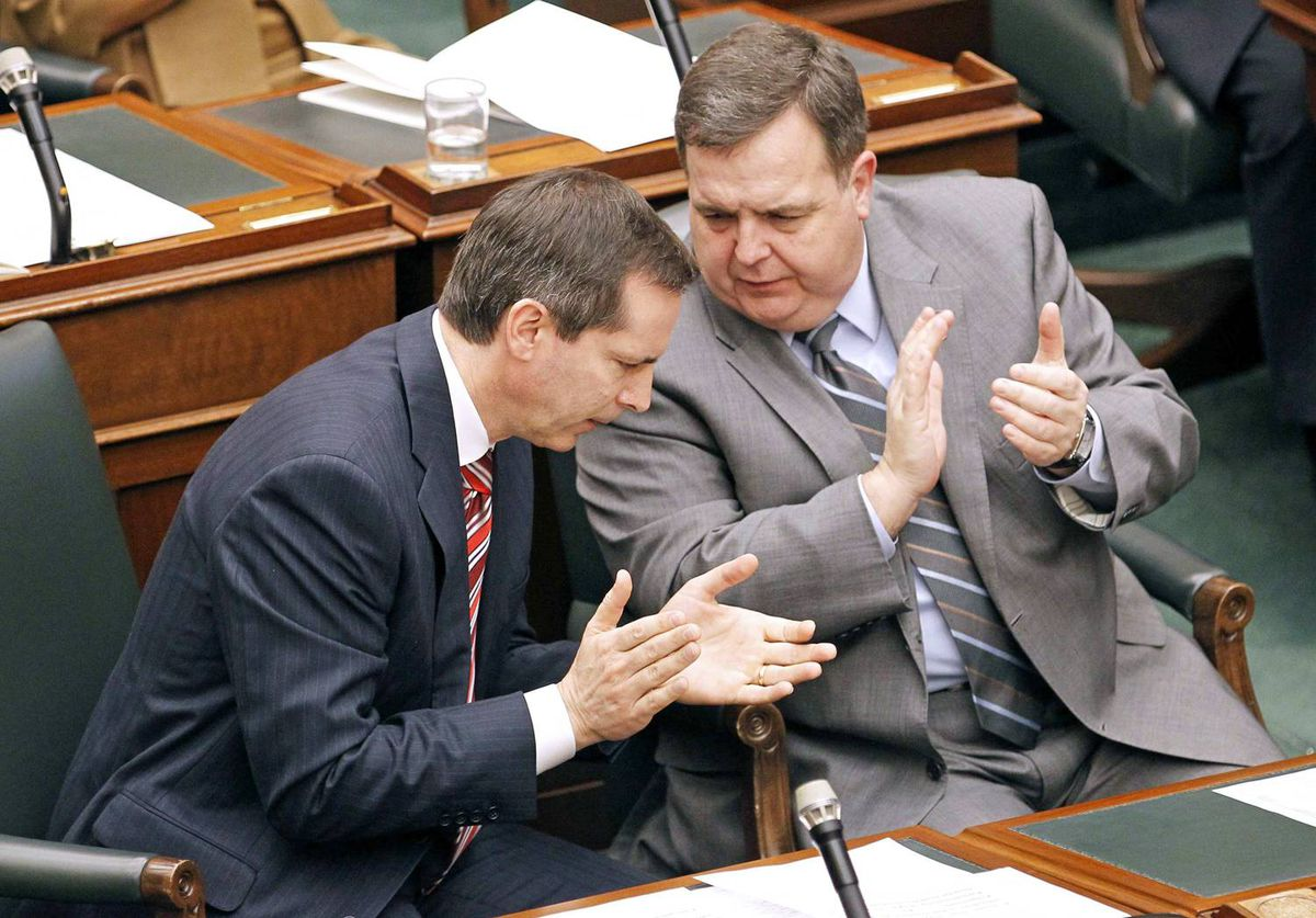 Premier Dalton McGuinty speaks with Finance Minister Dwight Duncan during the Speech from the Throne at the Ontario Legislature in Toronto on March 8, 2010.