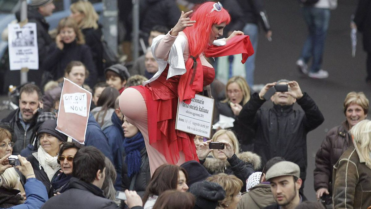 A woman on stilts mocking a prostitute amuses people marching against Italian premier Silvio Berlusconi during a protest in Milan, Italy, Sunday, Feb. 13, 2011.