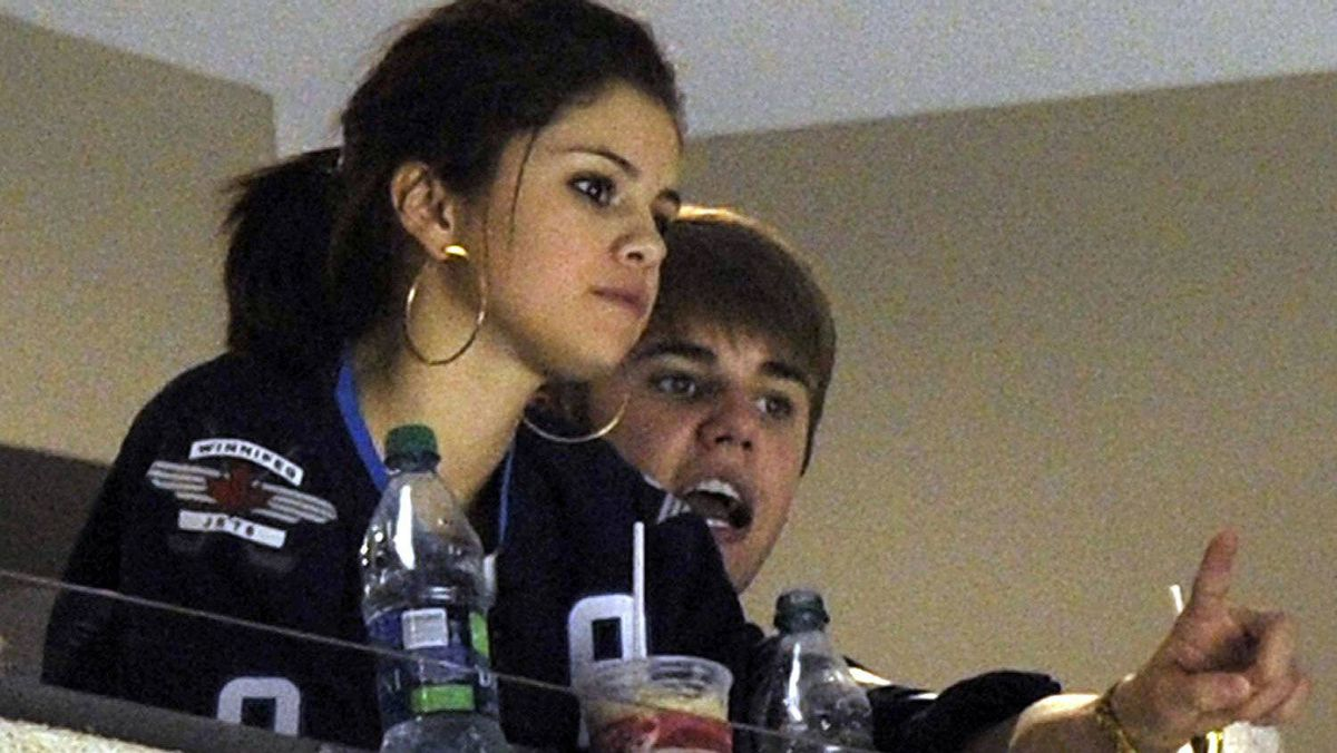 Singer Justin Bieber (R) and his girlfriend Selena Gomez watch the NHL game between the Carolina Hurricanes and Winnipeg Jets in Winnipeg October 22, 2011. REUTERS/Fred Greenslade