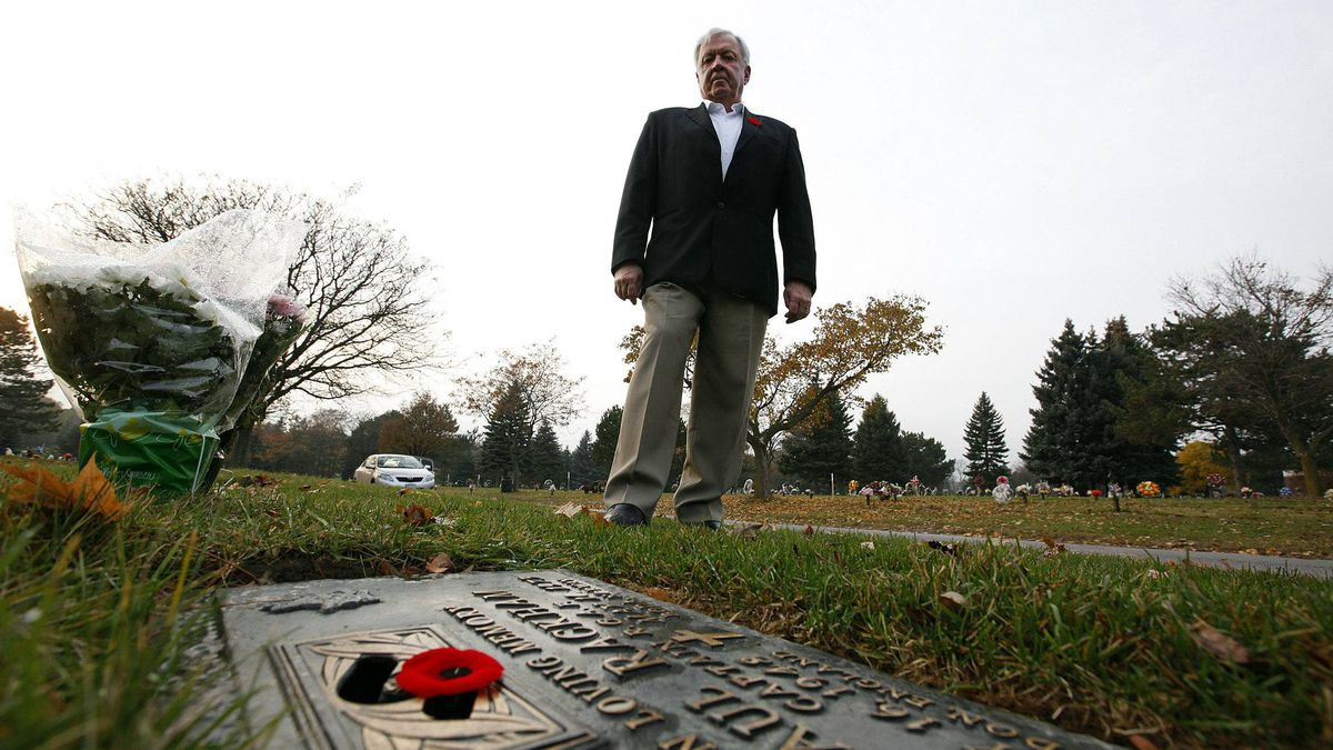 """Former fighter pilot, John """"Jock"""" Williams poses for a portrait at the grave marker of his friend, a former pilot Captain Paul Rackham at Holy Cross Cemetery in Thornhill, Ontario, Canada."""