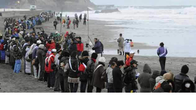 People join hands facing the sea to mourn victims of the 2011 earthquake and tsunami in Iwaki, Fukushima prefecture, on Sunday.