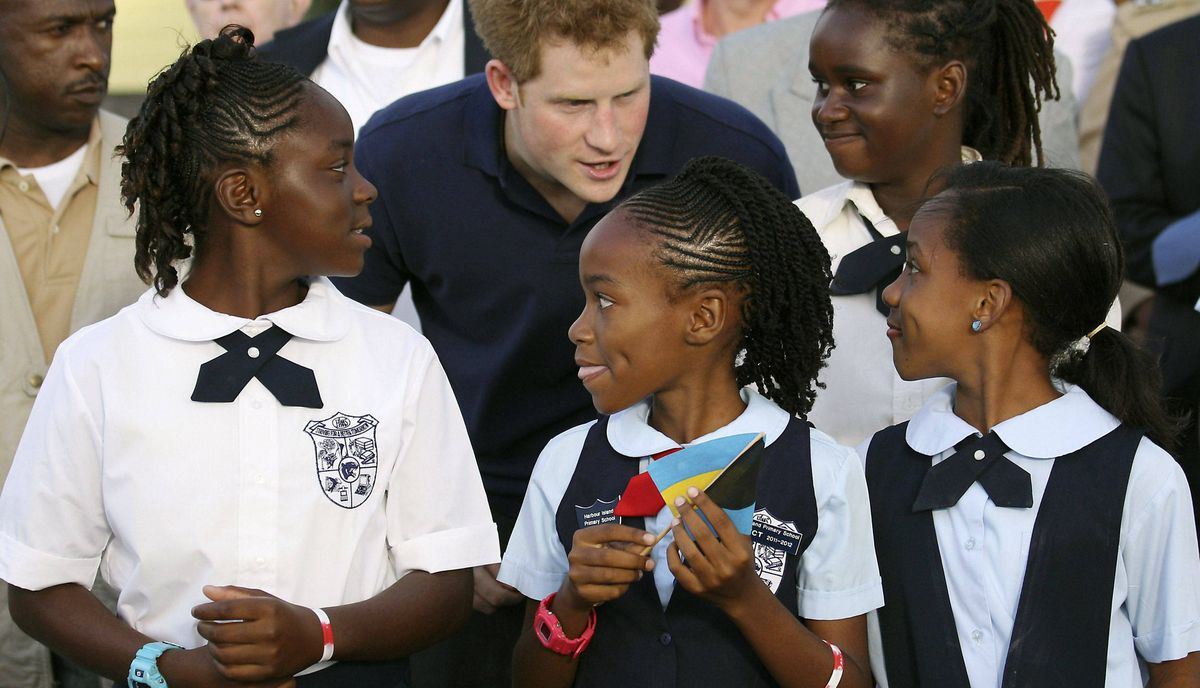 Prince Harry chats with some children during a tour of Harbour Island in Nassau on March 4, 2012.