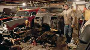 Luke Zentil stands next to the frame of a 1950 Buick Sedanette that he is building using a 1977 Mustang's suspension and a 1984 Mercedes' turbo diesel engine and independent rear suspension.