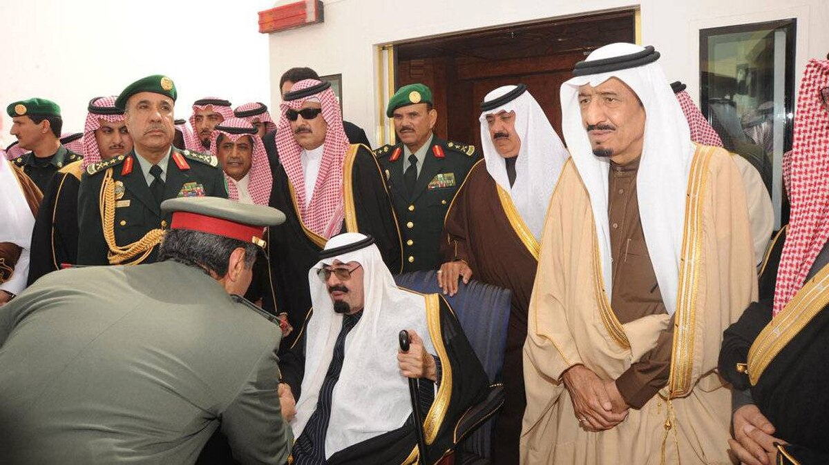 Saudi Arabia's King Abdullah (seated) is greeted by a Saudi officer on his arrival at Riyadh airport in this February 23, 2011 file photo.