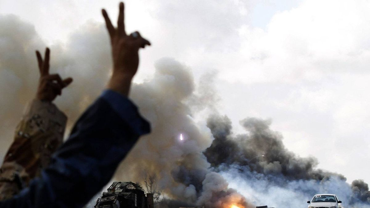 Rebel fighters gesture in front of burning vehicles belonging to forces loyal to Libyan leader Muammar Gaddafi after an air strike by coalition forces along a road between Benghazi and Ajdabiyah March 20, 2011.