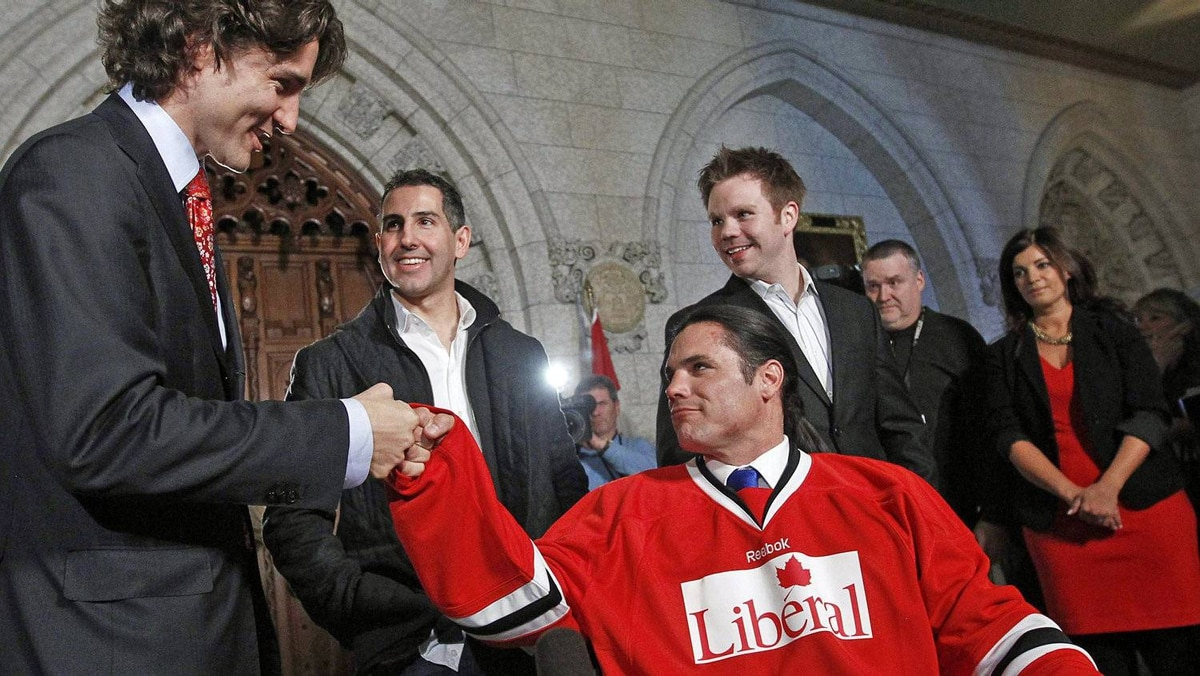 Justin Trudeau bumps fists with Patrick Brazeau after cutting off a lock of his hair in the foyer of the House of Commons on April 2, 2012. The Tory Senator agreed to have his hair cut after losing a charity boxing match to the Liberal MP.