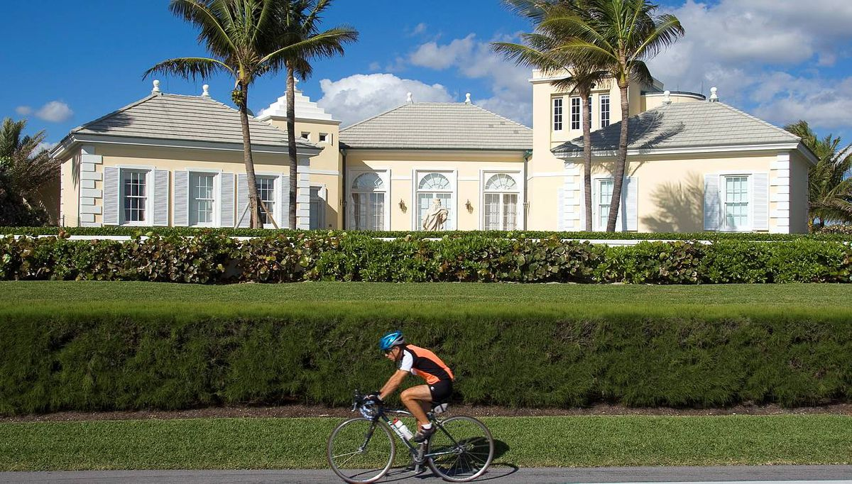 A cyclist rides along South Oceans Boulevard outside Conrad Black's former home in Florida.