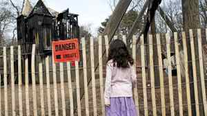 A child looks at the charred Jamie Bell Adventure Playground in Toronto's High Park that was suspected to have been deliberately set ablaze early Saturday morning.