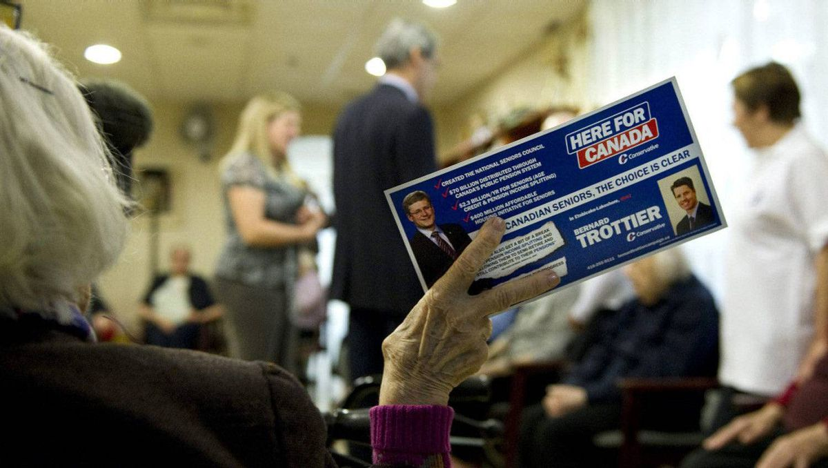A resident holds up a Conservative flyer as Liberal Leader Michael Ignatieff greets residents at an old age home on election day, Monday, May 2, 2011 in Toronto.