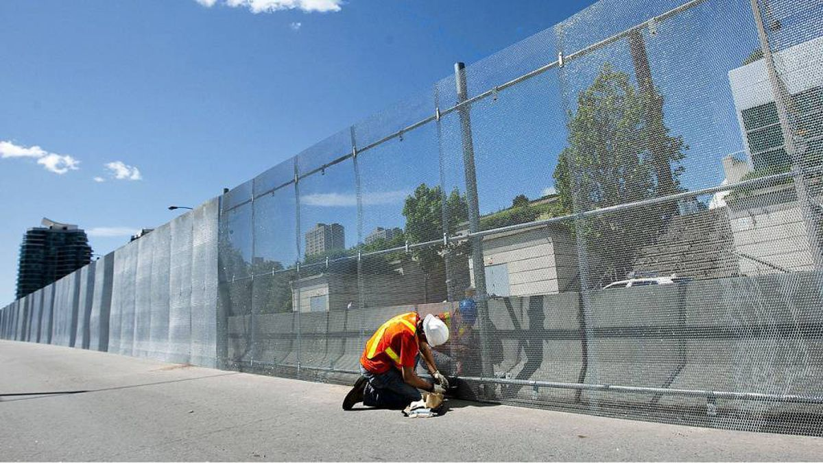 A construction worker puts up a three metre high steel security fence outside the Toronto Metro Convention Centre for the upcoming Toronto G20 summit in Toronto on Tuesday, June 8, 2010.