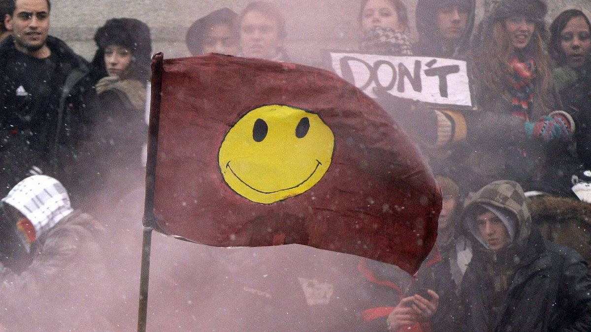 A protester raises a flag as hundreds of students rally against tuition fees at in London's Trafalgar Square on Nov. 30, 2010.