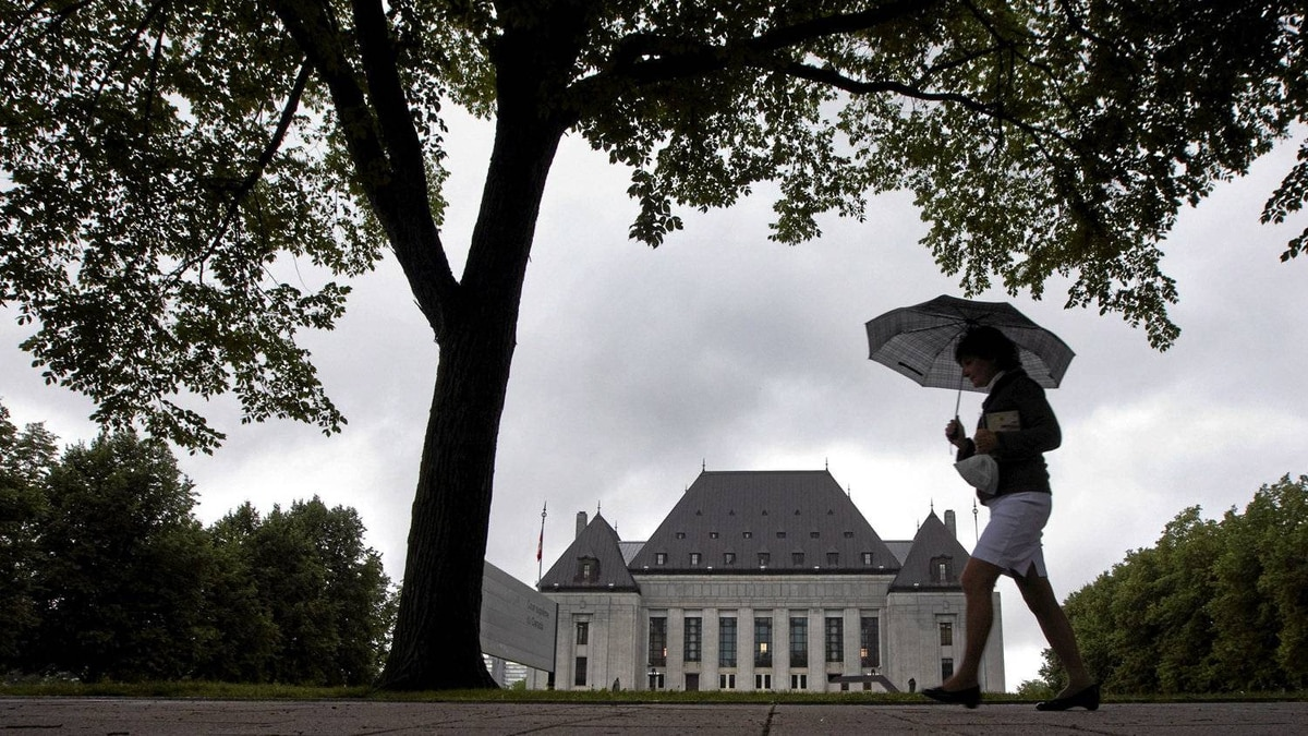 A pedestrian walks past the Supreme Court of Canada in Ottawa on Thursday June 10, 2010. The Supreme Court of Canada has upheld a defendant's right to have an automatic publication ban on evidence at their bail hearing.